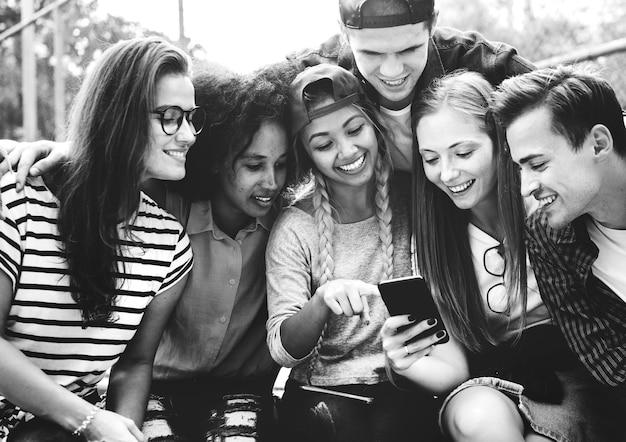 Vrienden in het park op zoek met behulp van smartphones millennial en jeugdcultuurconcept