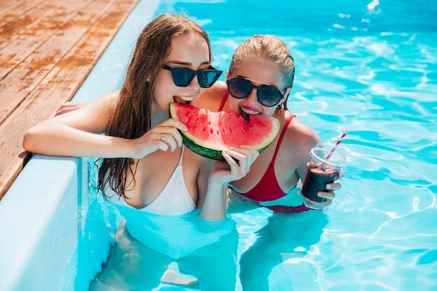 Vrienden in het zwembad eten een watermeloen