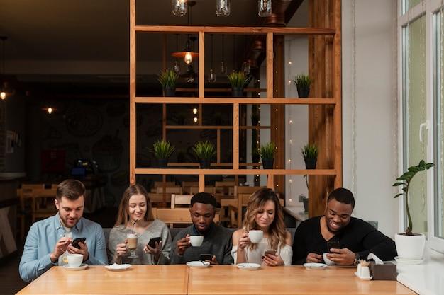 Vrienden in restaurant met behulp van telefoons