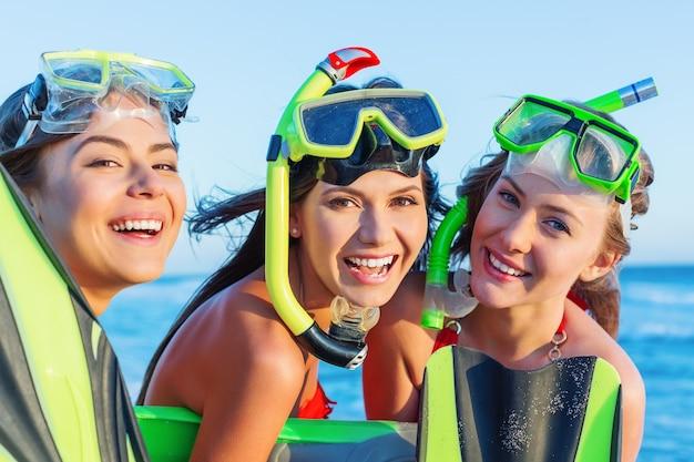 Vrienden in scuba-uitrustingen op zee achtergrond