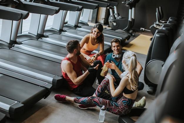 Vrienden in sportkleding praten en lachen samen zittend op de vloer van een sportschool na een training