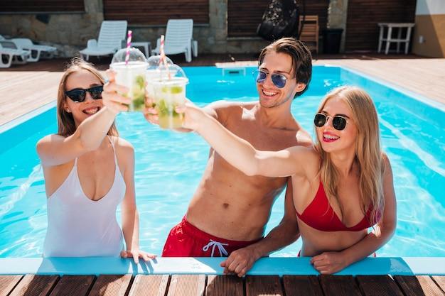 Vrienden juichen met cocktails in het zwembad