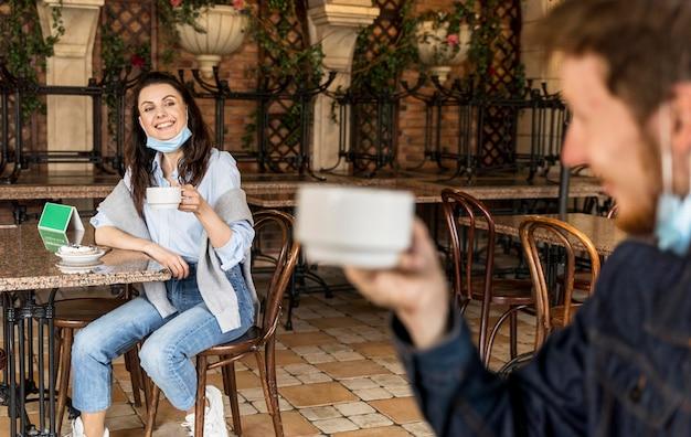Vrienden juichen met kopjes thee met respect voor de sociale afstand