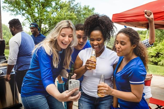 Vrienden kijken naar de wedstrijd op een telefoon op een achterklepfeestje