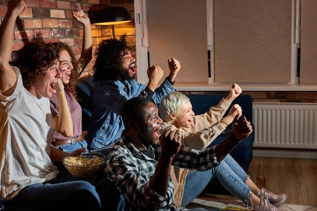 Vrienden kijken naar grote wedstrijden, juichen voor het beste team. sport, mensen, vrije tijd, vriendschap en geluk concept. 's avonds of 's nachts thuis, vrolijke kerel en dames vieren overwinning