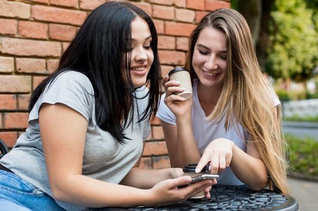 Vrienden kijken naar iets leuks op een slimme telefoon