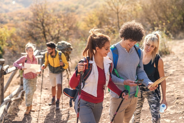 Vrienden kijken naar kaart en kompas. man met de krullende kaart en het kompas van de haarholding terwijl vrouwen het kijken. wandelen op herfst concept.