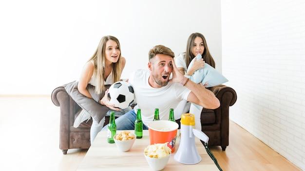 Vrienden kijken naar voetbal thuis