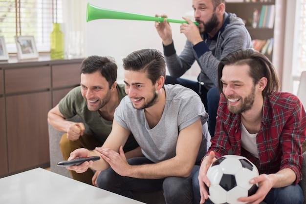 Vrienden kijken naar voetbalwedstrijd