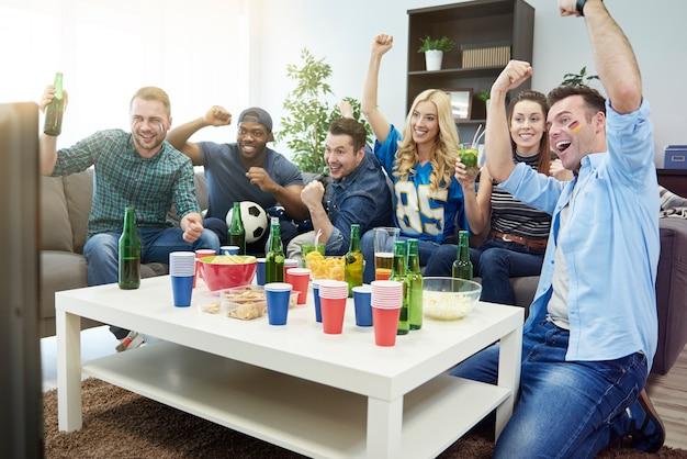 Vrienden kijken naar wedstrijd en hebben samen plezier