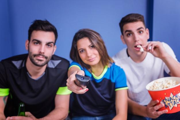 Vrienden kijken voetbal met popcorn