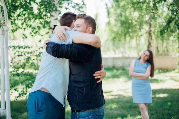 Vrienden knuffelen in berk bos
