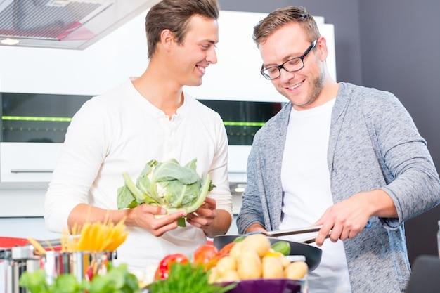 Vrienden koken van groenten en vlees in de binnenlandse keuken