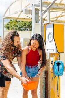 Vrienden krijgen water bij tankstation tijdens stop-off