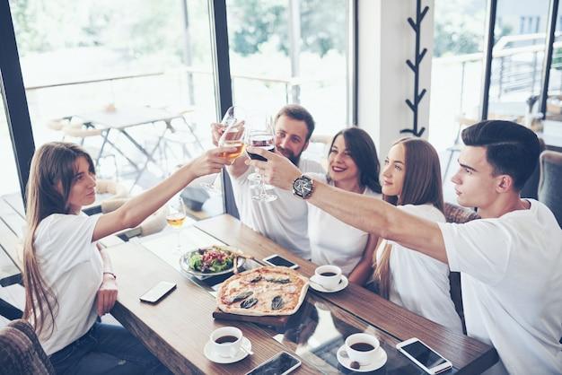 Vrienden kwamen aan tafel bij elkaar met heerlijk eten met glazen rode wijn om een speciale gelegenheid te vieren