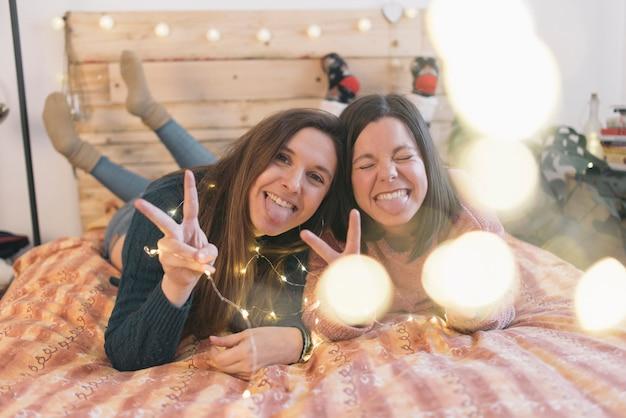 Vrienden liggend op bed en glimlachen. vriendschap concept