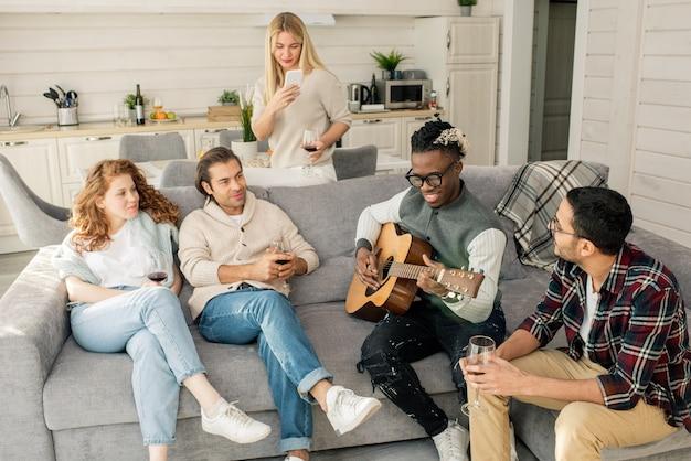 Vrienden luisteren naar man gitaar spelen