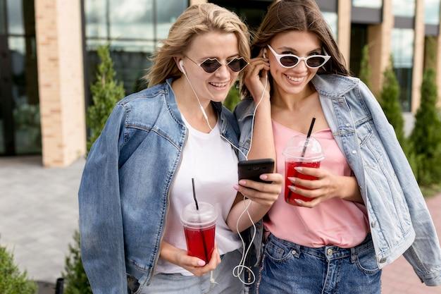 Vrienden luisteren naar muziek op oortelefoons