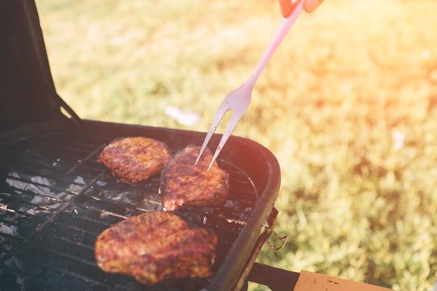 Vrienden maken barbecue en lunchen in de natuur. paar plezier tijdens het eten en drinken op een picknick - gelukkige mensen op bbq-feestje.