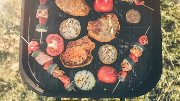 Vrienden maken barbecue en lunchen in de natuur. paar plezier tijdens het eten en drinken op een picknick - gelukkige mensen op bbq party.
