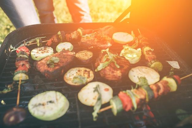 Vrienden maken barbecue en lunchen in de natuur. paar plezier tijdens het eten en drinken tijdens een picknick - happy people at bbq party