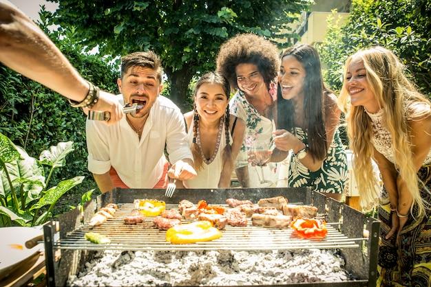 Vrienden maken barbecue in de tuin