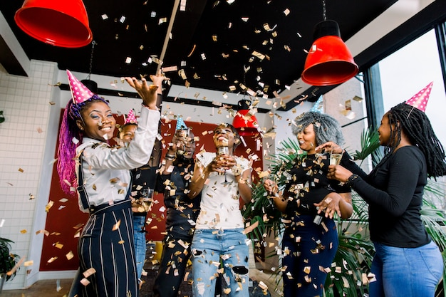 Vrienden maken groot feest in de nacht. zes afrikaanse mensen gooien confetti en drinken champagne