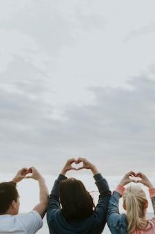 Vrienden maken liefdesharten op het strand