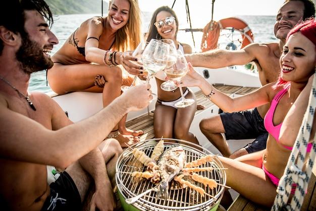 Vrienden maken vis barbecue op het jacht