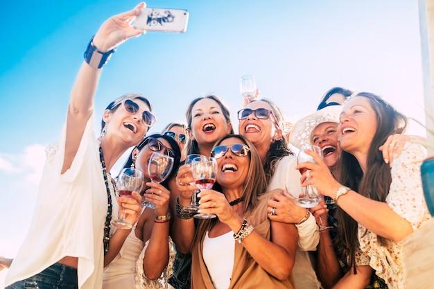 Vrienden mensen in groep hebben samen plezier in vriendschapsfeest met rode wijn en selfie foto van telefoon