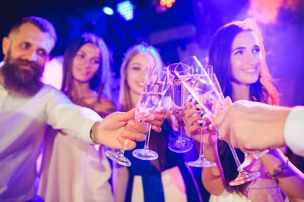 Vrienden met alcoholische dranken op een feestje.