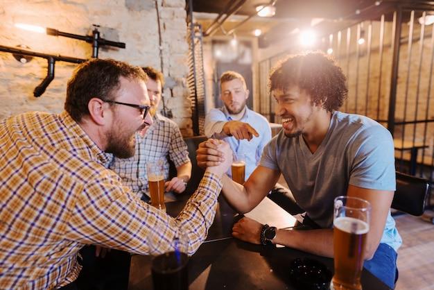 Vrienden met arm worstelen in pub.