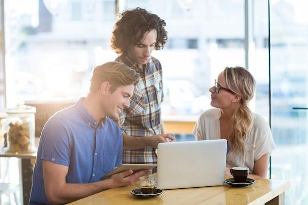 Vrienden met behulp van digitale tablet en laptop in café