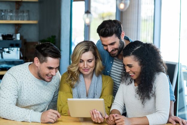 Vrienden met behulp van digitale tablet in café