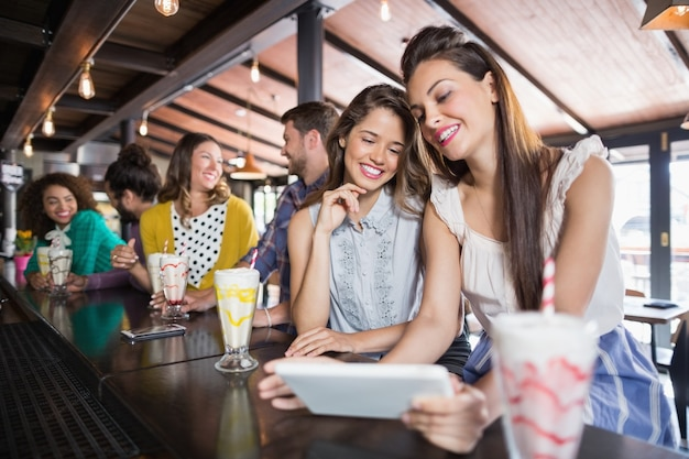 Vrienden met behulp van digitale tablet in restaurant
