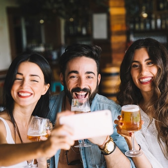 Vrienden met bier poseren voor selfie