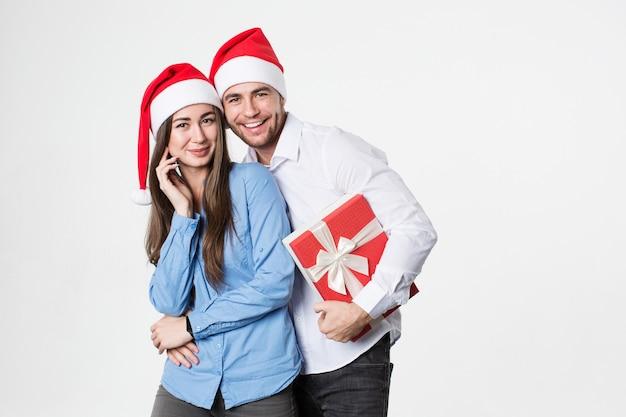 Vrienden met cadeau voor nieuwjaar en kerstmis in kerstmuts geïsoleerd