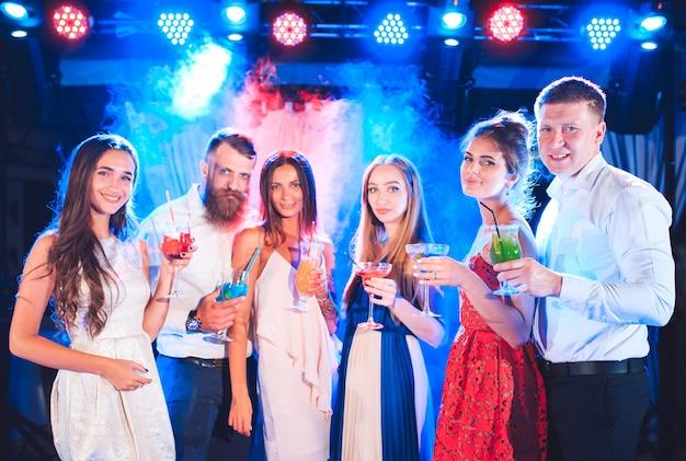 Vrienden met cocktails drinken op een feestje.