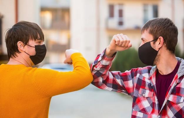 Vrienden met een beschermend medisch masker op zijn gezicht begroeten hun ellebogen in quarantaine