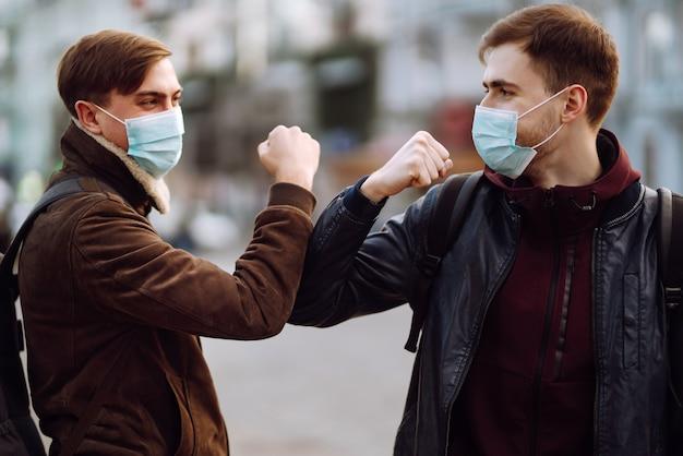 Vrienden met een beschermend medisch masker op zijn gezicht begroeten hun ellebogen