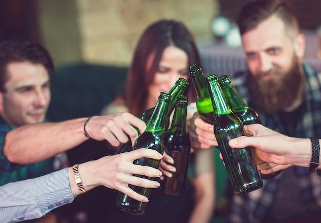 Vrienden met een drankje in een bar, ze zitten aan een houten tafel met bier en pizza.
