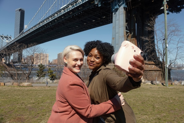 Vrienden met een middelgroot shot die buitenshuis selfies maken