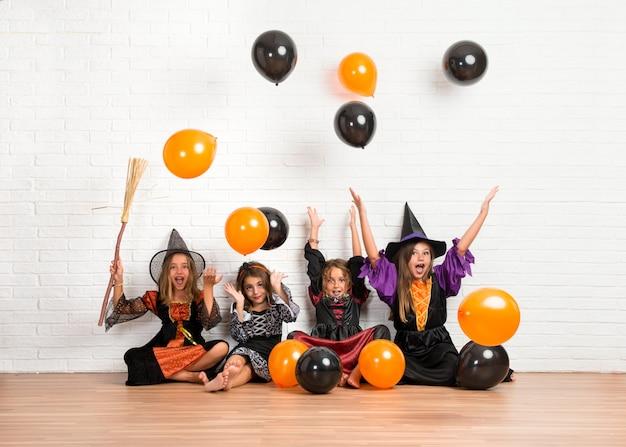 Vrienden met kostuums van vampieren en heksen voor halloween-vakantie die met ballons spelen