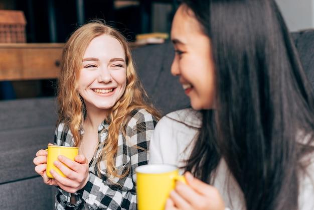 Vrienden met thee mokken glimlachen