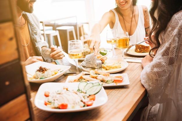 Vrienden met verschillende gerechten van eten