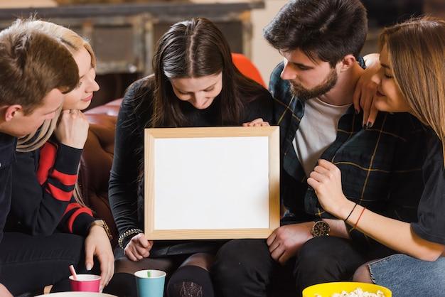 Vrienden met whiteboard op een feestje