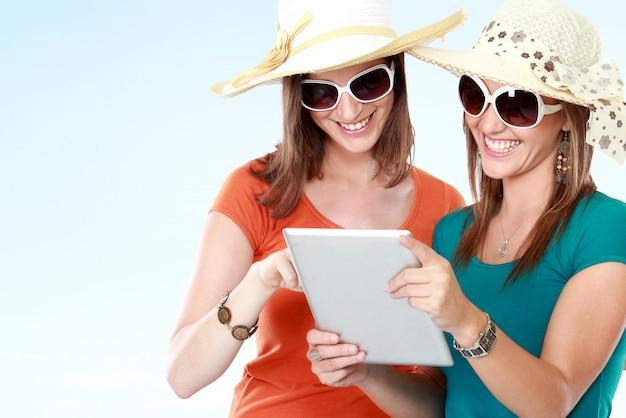 Vrienden met zonnebril die tablet gebruiken