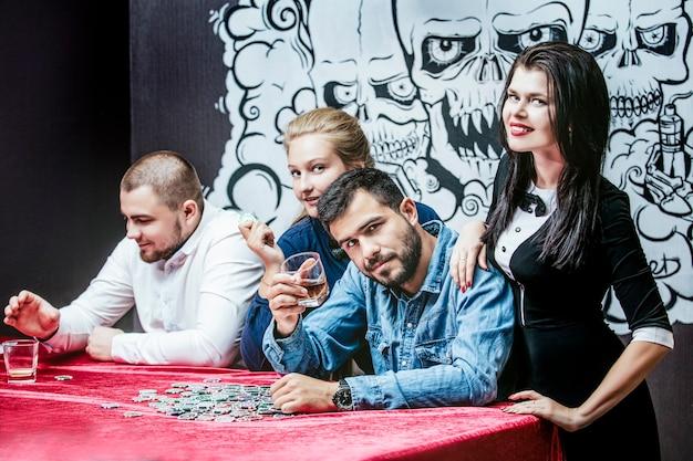 Vrienden mooie jonge succesvolle gokken in casino speel je poker aan een tafel met chips