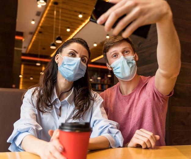 Vrienden nemen een selfie in een restaurant terwijl ze een medisch masker dragen
