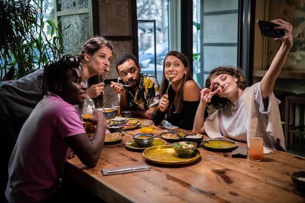 Vrienden nemen foto's van zichzelf in een café tijdens een feestje